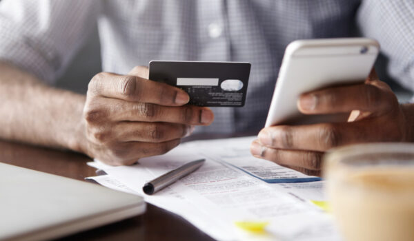 close-up-view-african-man-s-hands-holding-plastic-credit-card-smartphone